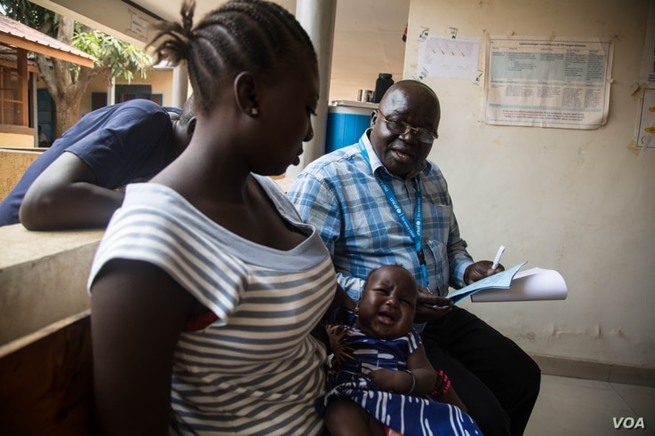 UNICEF health specialist Dr. Patti Samuel (R) explains the importance of childhood immunizations to a young mother. (Chika Oduah/VOA)