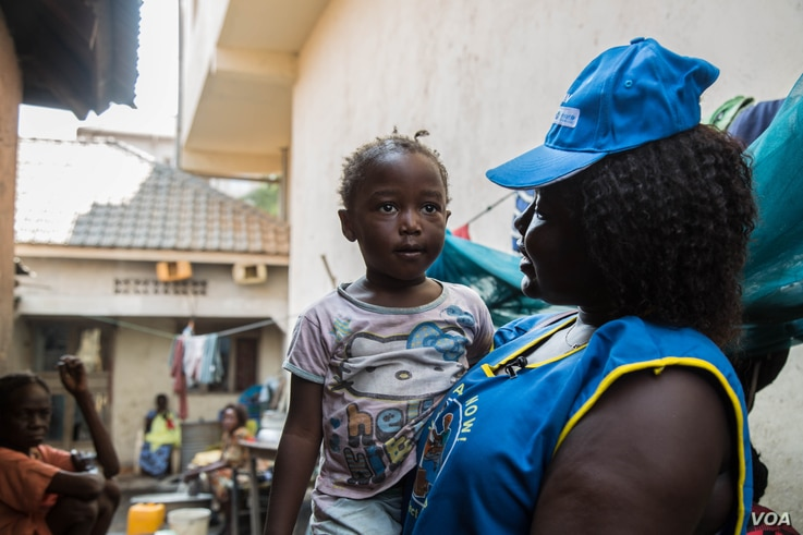 Agnes Anjack Alphonse, a UNICEF community health volunteer, tells a little girl that she needs to get vaccinated against measles. (Chika Oduah/VOA)