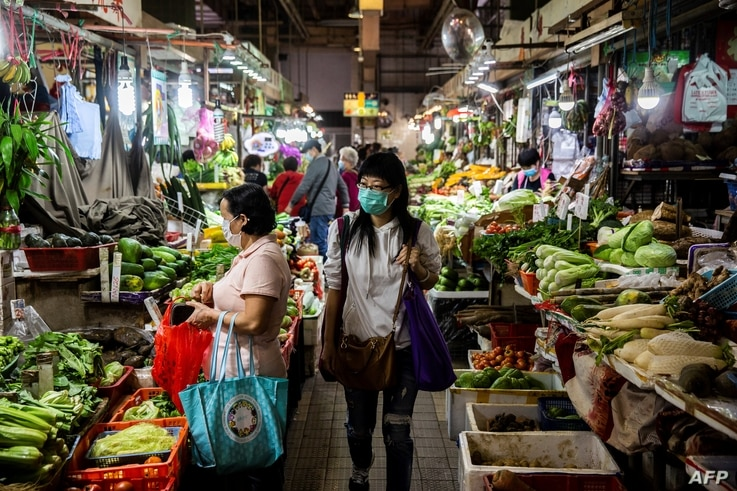 A women (C) walks through the wet markets wearing a protective face mask in Hong Kong on February 25, 2020. - The new…