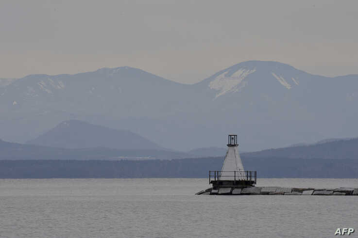 A view as the sun tries to breakthrough the clouds looking towards New York State from Burlington Bay Lake Champlain in…