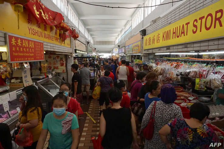 Customers visit a wet market to buy food in Singapore on April 4, 2020, with some people wearing facemasks due to concerns over…