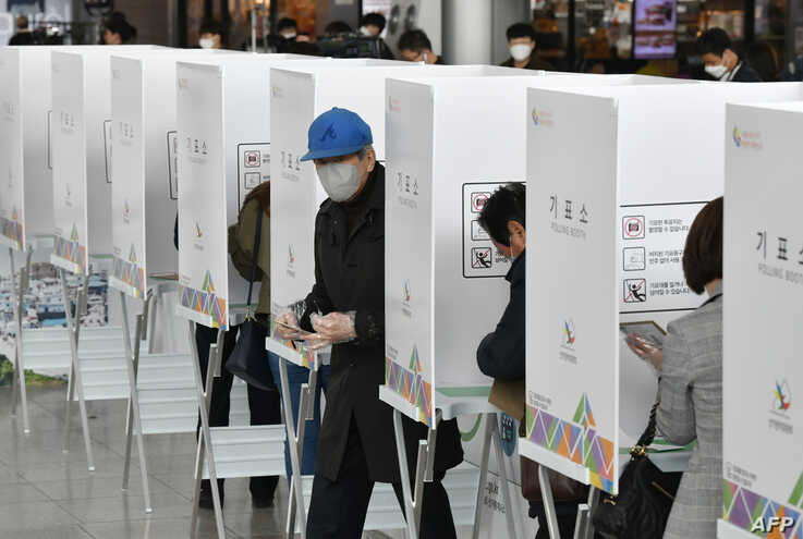 A South Korean man casts a ballot during early voting at a polling station in Seoul on April 10, 2020, ahead of next week's…