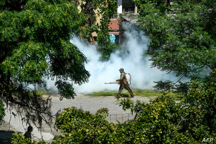 A worker sprays disinfectant in a residential area during a government-imposed nationwide lockdown as a preventive measure…