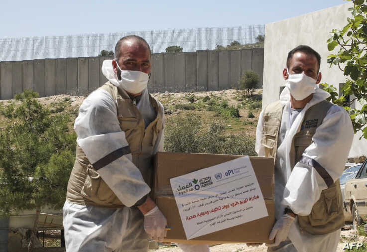 Members of the French Action Against Hunger NGO distribute hygiene and sanitation products to Palestinian residents of al…