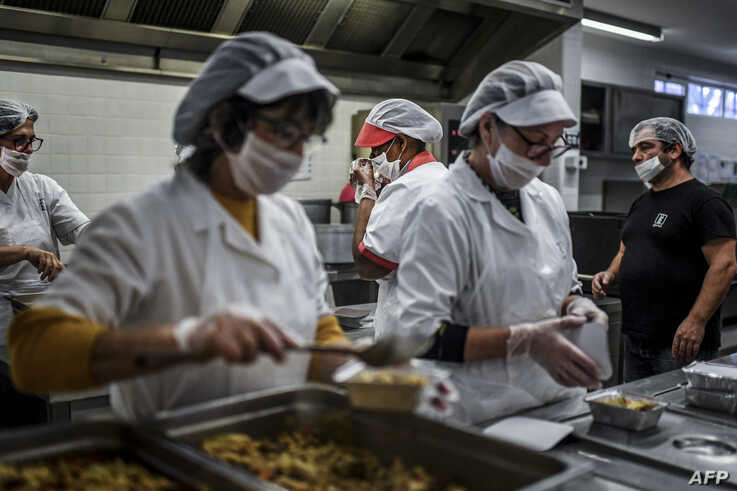 School canteen workers prepare meals to be distributed to people as part of an emergency plan by the Lisbon city hall to…