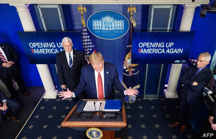 US President Donald Trump flanked by US Vice President Mike Pence and Director of the National Institute of Allergy and…