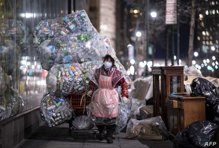 A woman wearing a face mask and a plastic bag pulls a cart loaded with bags of recyclables through the streets of Lower…