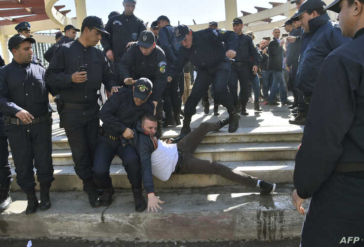 (FILES) In this file photo taken on February 28, 2019 Algerian policemen detain a protester participating in a rally organised…