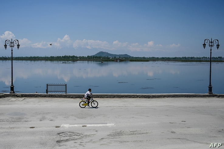 A boy rides a bicycle along the bank of the Dal Lake