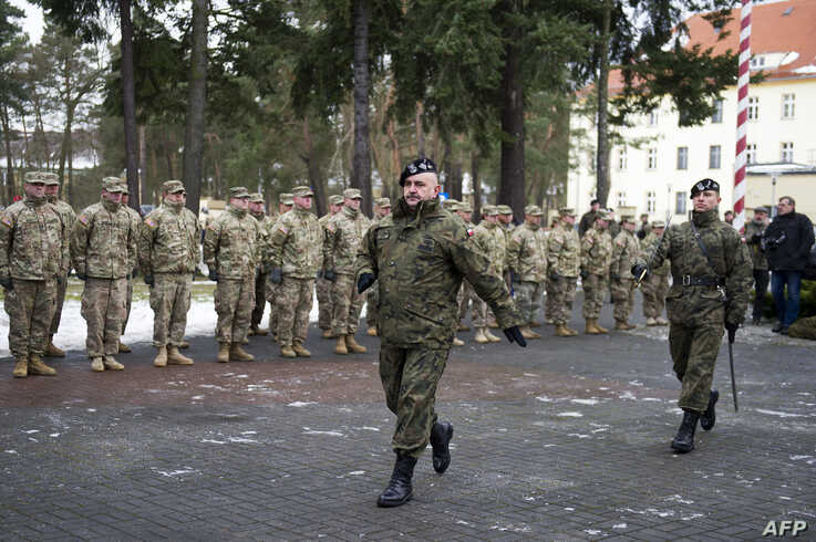 General Jaroslaw Mika marching before US soldiers during the welcome ceremony at the Polish military base in Zagan, Poland on…