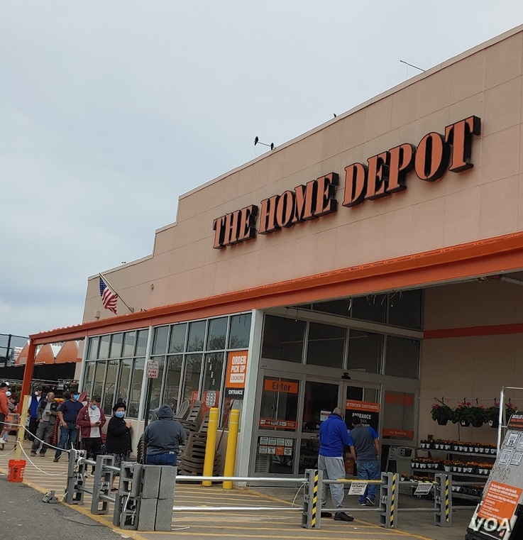 """Customers maintain """"social distancing"""" while waiting in line to get into a Home Depot in Alexandria, Virginia that is limiting t"""