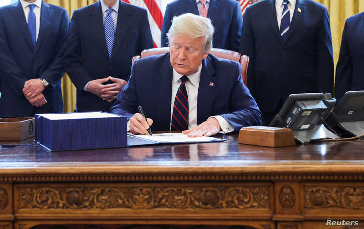 U.S. President Donald Trump signs the $2.2 trillion coronavirus aid package bill as he sits at the Resolute Desk in the Oval…