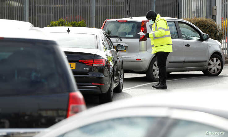 People queue in their cars at an NHS drive-through coronavirus disease (COVID-19) testing facility in the car park of Ikea in…