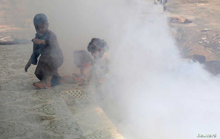 Children are seen amidst smoke from fumigation at a market during fumigation campaign while the spread of the coronavirus…