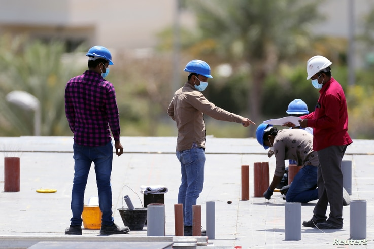Workers wearing protective face masks work on a residential construction site, following the outbreak of coronavirus disease (COVID-19), in Dubai, United Arab Emirates, April 14, 2020.