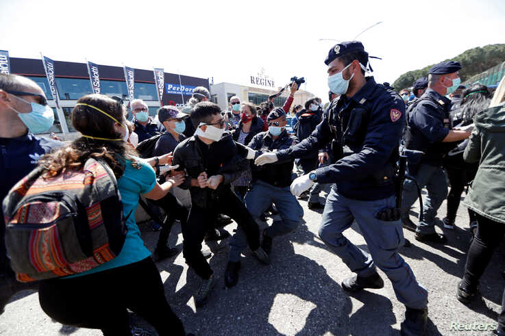 Police surround protesters wearing protective face masks as they demonstrate outside the Rebibbia prison to demand better…