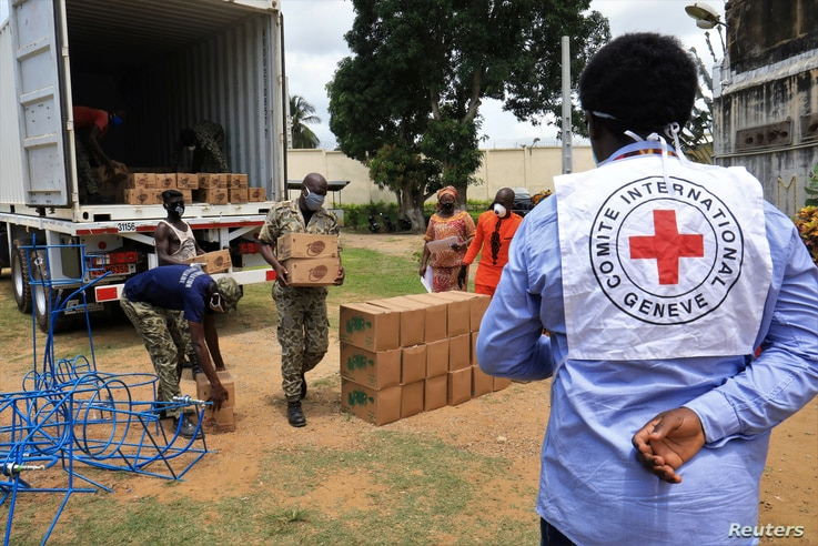 Guards from a civil prison unload an International Committee of the Red Cross (ICRC) truck containing sanitary kit amid the…
