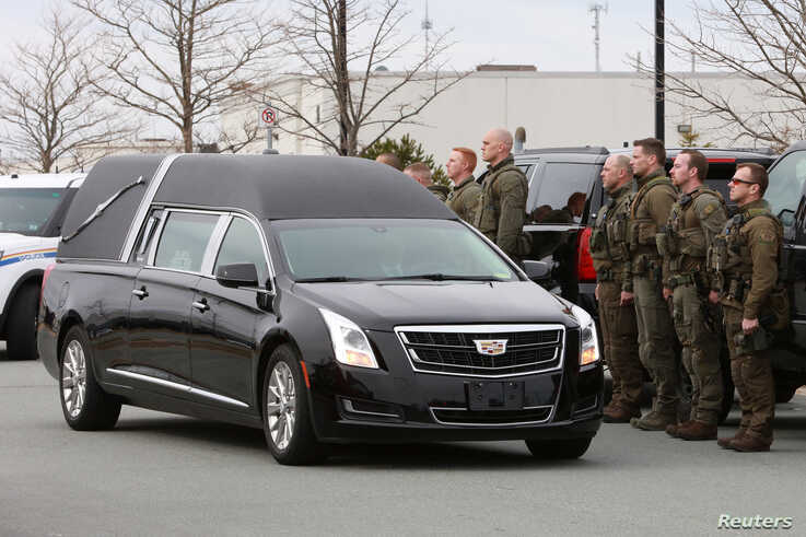 Royal Canadian Mounted Police (RCMP) officers stand in line for a procession as a hearse carrying the body of Constable Heidi…