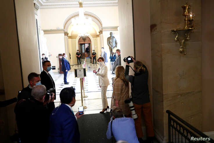 U.S. Speaker of the House Nancy Pelosi (D-CA) wears a face mask as she walks to the House Chamber ahead of a vote on an…