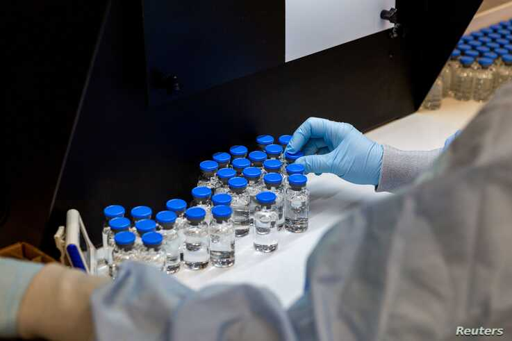 A lab technician inspects filled vials of investigational coronavirus disease (COVID-19) treatment drug remdesivir at a Gilead…