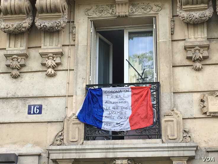 A French flag outside a Paris appartment urging people to stay at home and thanking health care workers. (Lisa Bryant/VOA)