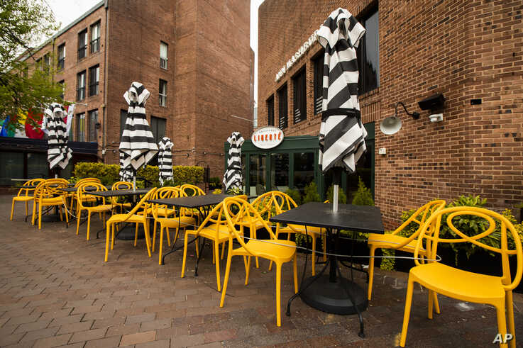 Empty chairs lines a sidewalk outside a restaurant Washington's Georgetown district, April 29, 2020.