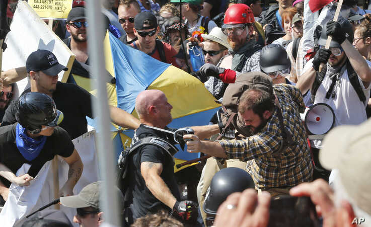FILE - In this Aug. 12, 2017 file photo, white nationalist demonstrators clash with counter demonstrators at the entrance to…