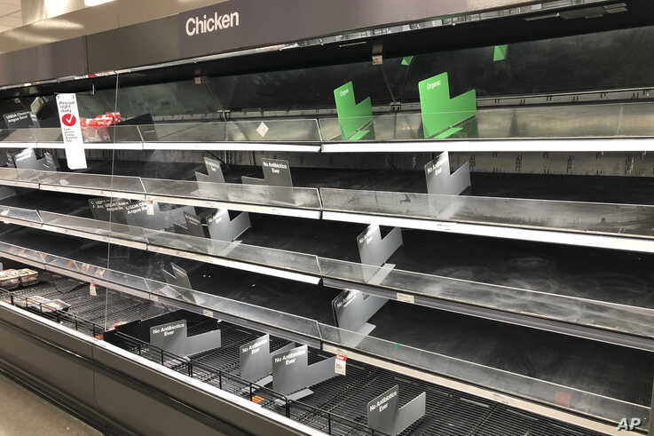 Shelves that usually hold an abundance of chicken and beef lay empty at a Target in Abington, Pa., Wednesday, March 18, 2020…
