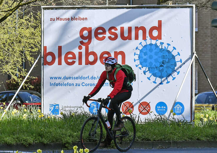 "A man cycles by an advertisement reading ""stay home, stay healthy"" in Duesseldorf, Germany, Monday, March 23, 2020.  In order…"