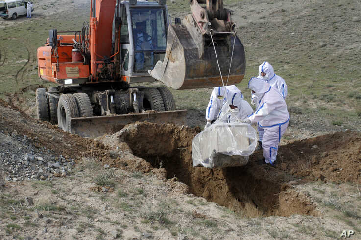 The municipality workers bury the body of coronavirus victim on the outskirts of Herat province west of Kabul, Afghanistan,…