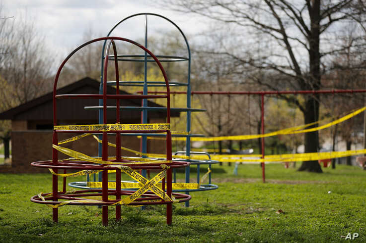 Playground equipment is wrapped in crime scene tape to prevent its use as part of the effort to slow the spread of the coronavirus March 31, 2020, in St. Louis.