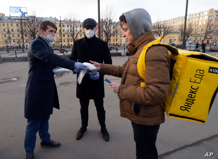 Volunteers give a face mask to a food delivery courier during an action for free distribution of masks protesting against price…
