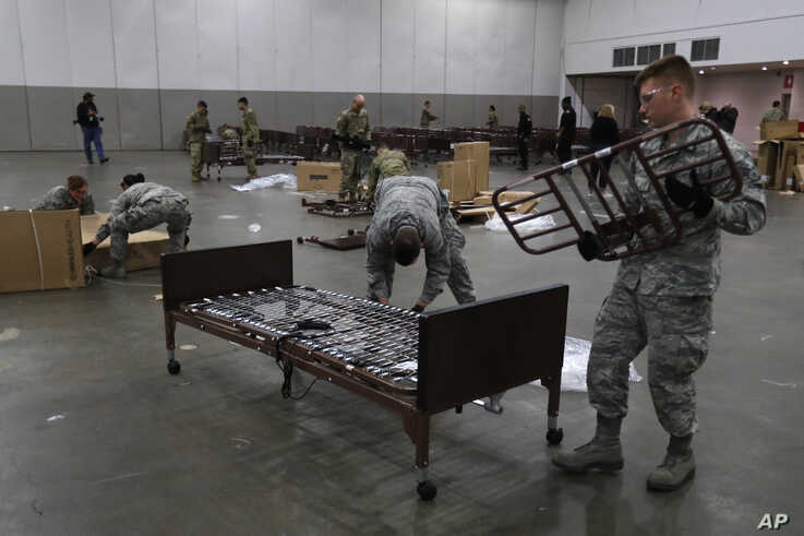 Members of the military assemble some of the beds, Wednesday, April 1, 2020 for use at TCF Center in Detroit to accommodate an…