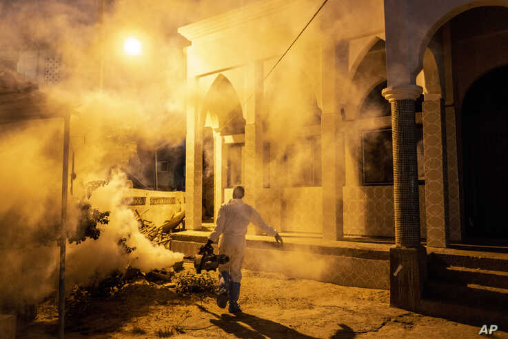 In this Wednesday, April 1, 2020, photo, a municipal worker sprays disinfectant in a mosque to help curb the spread of the new…