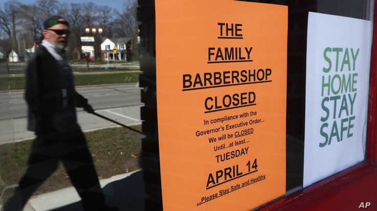 A pedestrian walks by The Family Barbershop, closed due to a Gov. Gretchen Whitmer executive order, in Grosse Pointe Woods,…
