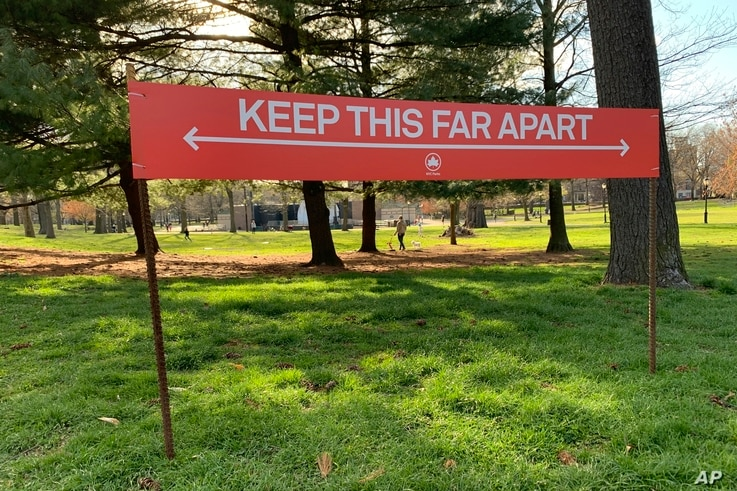 Signage urging social distancing is seen in Prospect Park in the Brooklyn borough of New York, Wednesday, April 8, 2020. While…