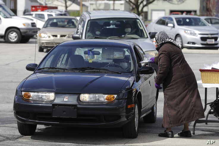 Bertha Brown hands a plastic bag filled with bread and a cup to a church member during a drive-thru Holy Communion on Good…