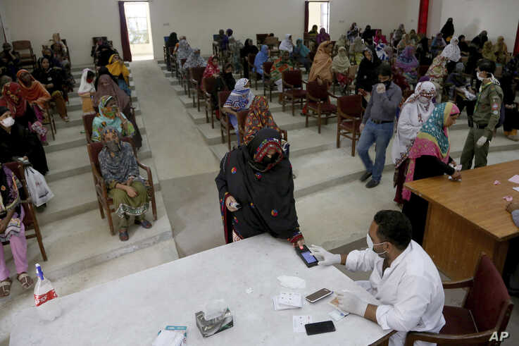 A woman scans her thumb for identification to receive cash under the governmental Ehsaas Emergency Cash Programme for families in need, during a government-imposed nationwide lockdown, Karachi, Pakistan, April 11, 2020.