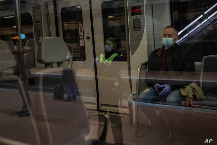 Commuters wearing face masks to protect against coronavirus at Atocha train station in Madrid, Spain, Monday, April 13, 2020.