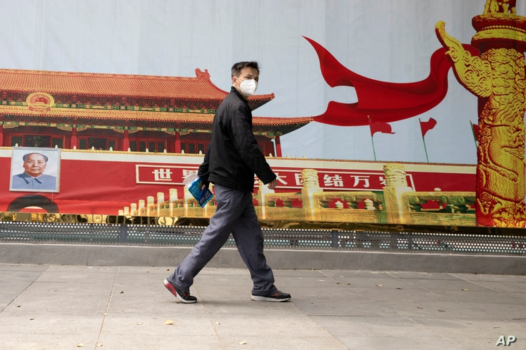 A resident wearing a mask against coronavirus walks past government propaganda poster featuring Tiananmen Gate in Wuhan