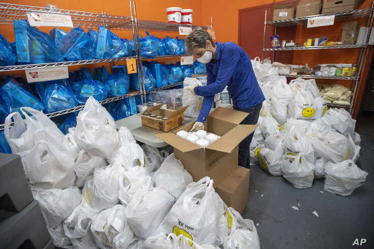 A volunteer prepares bags with groceries for delivery at The Campaign Against Hunger food pantry, Thursday, April 16, 2020, in the Bedford-Stuyvesant neighborhood of the Brooklyn borough of New York.