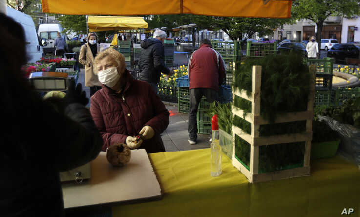A woman shops as the farmers markets open in Prague, Czech Republic, Monday, April 20, 2020. Czech Republic has started to ease…