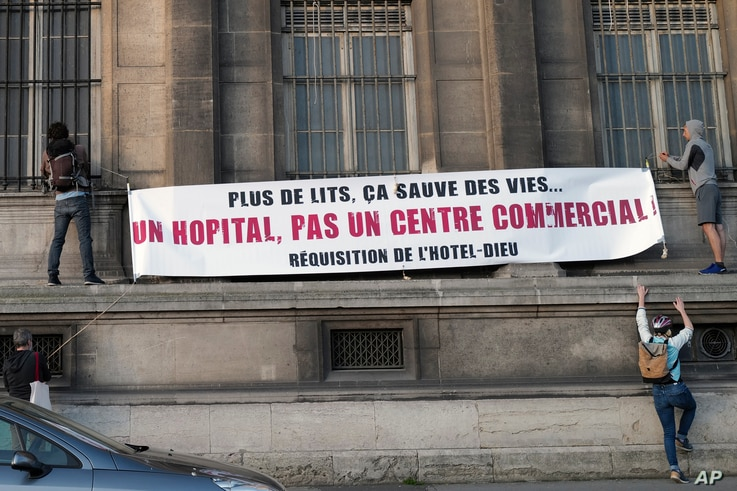 """Activists install a banner reading """"More beds can save lives, a hospital not a commercial center, requisition of the Hotel Dieu…"""