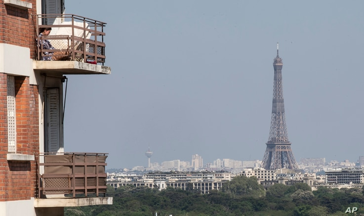 A woman enjoys the sun on her balcony as the Eiffel Tower is clearly seen in the background during the nationwide confinement…