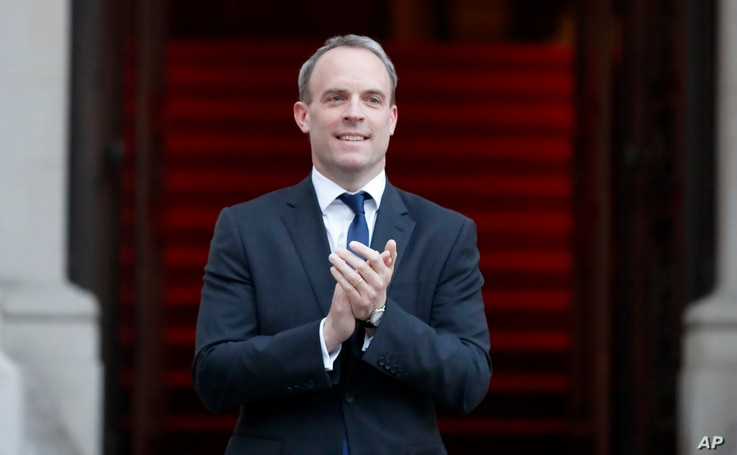 """Britain's Foreign secretary Dominic Raab applauds at the Foreign Office in London during the weekly """"Clap for our Carers"""" in…"""