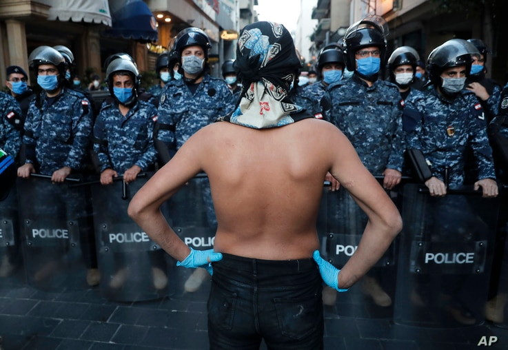 An anti-government protester stands in front of the Lebanese riot police who wear masks to help curb the spread of the…
