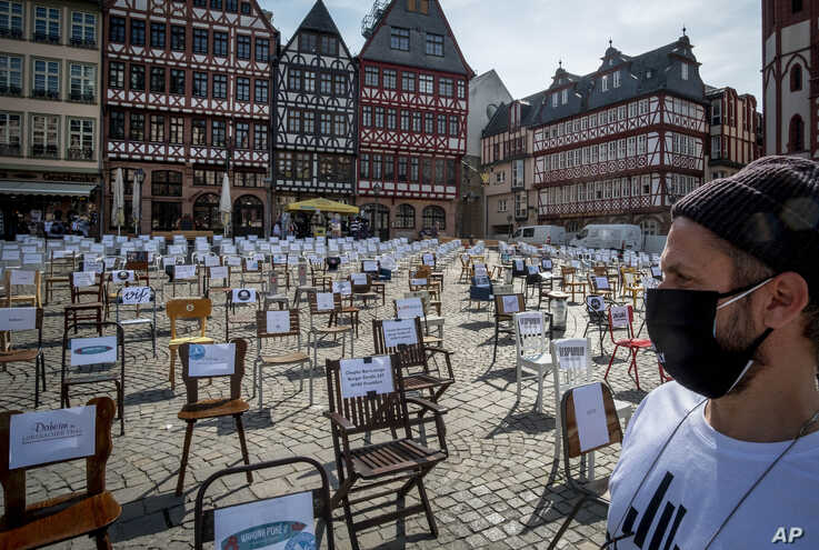 APTOPIX A man with a face mask watches empty chairs with names of bars and restaurants on the Roemerberg square in Frankfurt,…