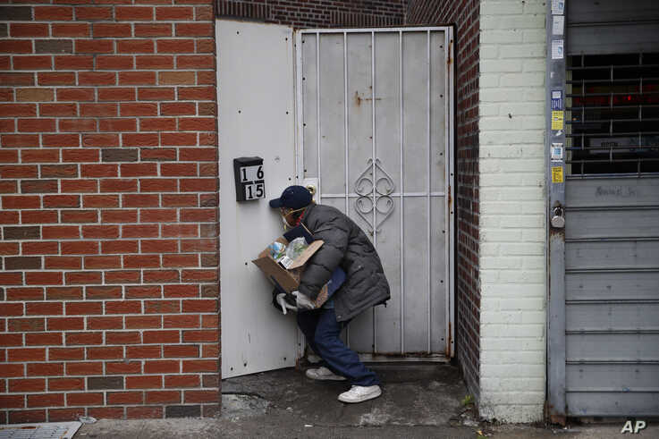 Francisco Ramirez peers through a hole in a fence while looking for an address to deliver a box of groceries to a man in need Saturday, April 18, 2020, in the Queens borough of New York.