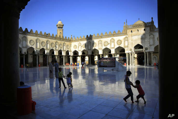 FILE - Egyptian children play as their family awaits the afternoon prayer on the first Friday of the holy month of Ramadan inside the Al-Azhar mosque, in Cairo, Egypt, June 19, 2015.