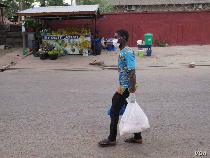 Oliver Tetteh carries packages of staple foods to distribute to households in Ghana's capital Accra, a city which has been in a partial lockdown since March 30, with many people out of work. (Stacey Knott/VOA)